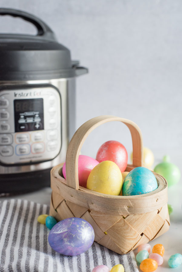 A basket of decorated Easter eggs placed in front of an Instant Pot.