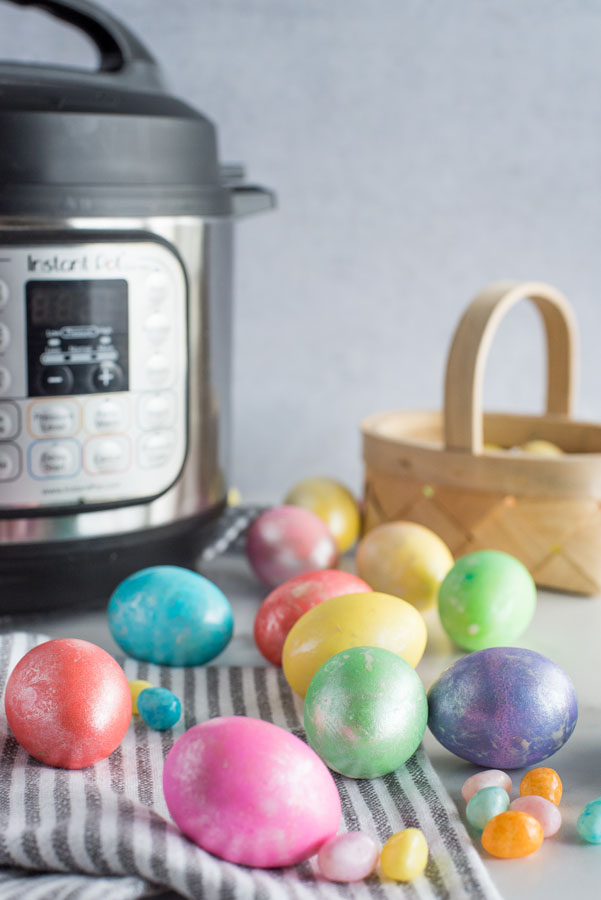 Easter eggs spread out on a table with jellybeans in front of an Instant Pot.