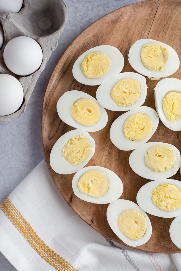 Overhead of a round wooden board with many perfectly cooked Instant Pot hard-boiled eggs cut in half with yellow yolks and firm egg whites.