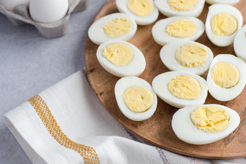 OVerhead of a round wooden board with Instant Pot hard-boiled eggs cut in half on a white and yellow striped dishcloth.
