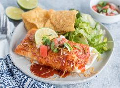 White dinner plate filled with tortilla chips, romaine lettuce and an Instant Pot Chili Colorado Smothered Burrito topped with melty cheese, lime wedge, fresh salsa and more enchilada sauce on a white background with a blue and white napkin and a silver fork.