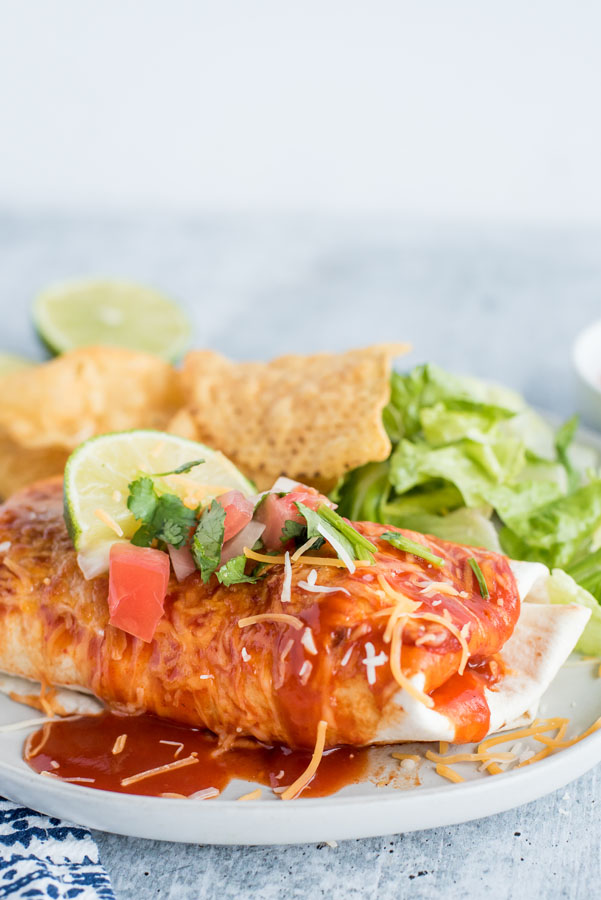 Close up on a freshly made Instant Pot / pressure cooker Chile Colorado smothered burrito with red echnilada sauce, melted Colby jack cheese, fresh salsa, cilantro, a lime wedge served with tortilla chips and crunchy romaine lettuce.