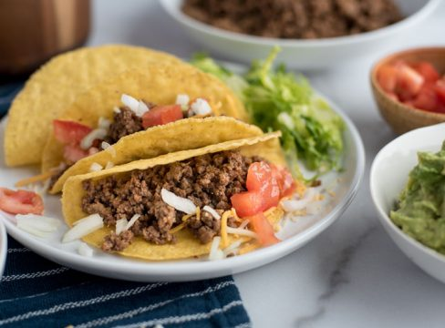 Instant Pot tacos in hard shells on a white plate with tomatoes, onions, cheese, and lettuce, next to bowls with guacamole and tomatoes.