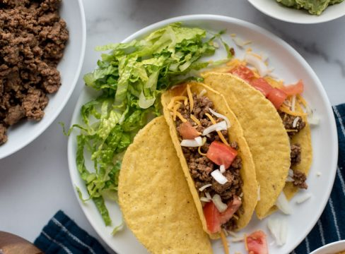 Overhead shot of ground beef tacos prepared in hard shells with tomatoes, cheese, onions, and lettuce on a white plate, sitting next to a bowl with cooked ground beef.
