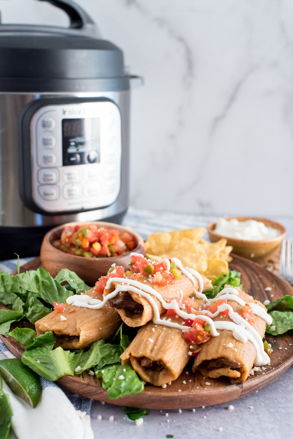 Wooden serving plate of four Instant Pot pork tamales made with masa and wrapped in corn husks with sour cream, fresh salsa, lettuce, tortilla chips and limes with an electric pressure cooker in the background.
