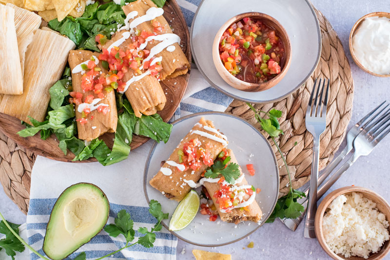 Overhead shot of Instant Pot Pork Tamales, featuring a large serving platter with tamales, two tamales plated up, and a bowl full of servings, with cilantro and avocado on the page
