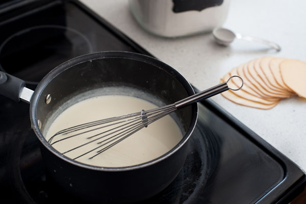 Preparing the Gouda cream sauce with a whisk on the stovetop  in a pan