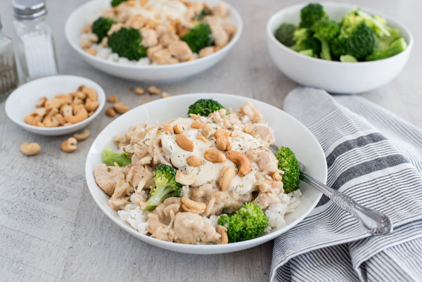 45 degree shot of rosemary cashew chicken in a serving bowl with rice and broccoli.