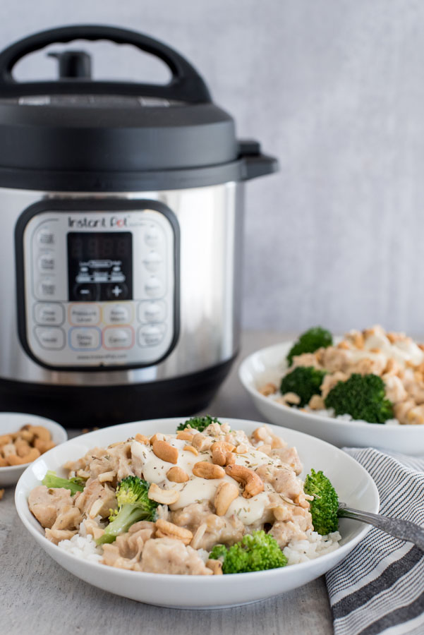 45 degree shot of a rosemary cashew chicken in a bowl with rice, cashews, and broccoli. Set in front of an Instant Pot.