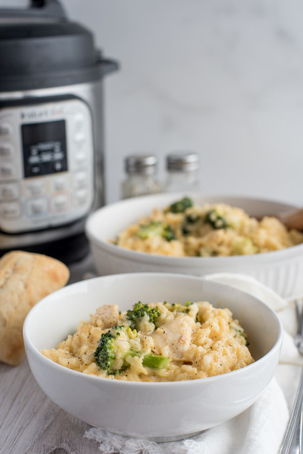 Cheesy chicken and broccoli in a white bowl with an Instant Pot in the background.