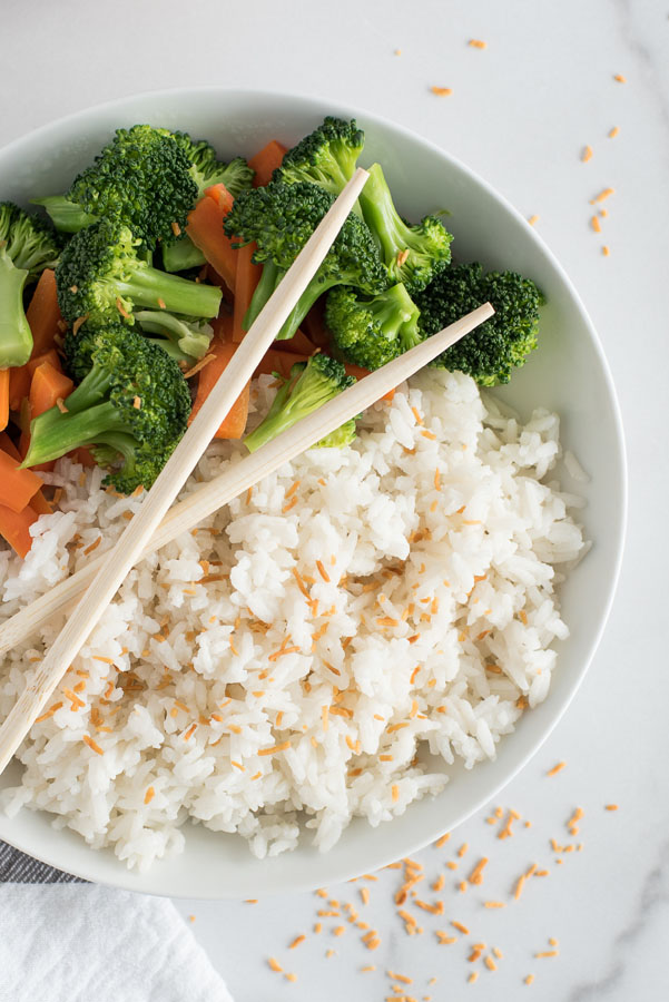 close up on a white dish of instant pot coconut rice topped with toasted coconut flakes with steamed broccoli and carrots and two wooden chopsticks crossed on top of the dish