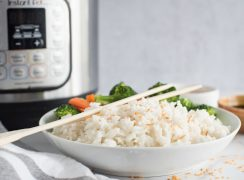 Side view of a white dish filled with instant Pot coconut rice topped with toasted coconut flakes and wooden chopsticks in front of an electric pressure cooker on a white and grey background