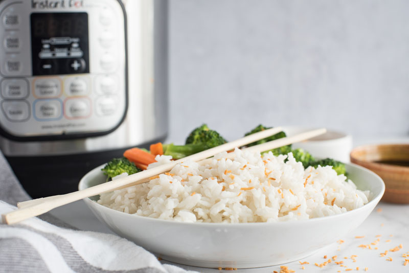Side view of a white dish filled with instant Pot coconut rice topped with toasted coconut flakes and wooden chopsticks in front of an electric pressure cooker.
