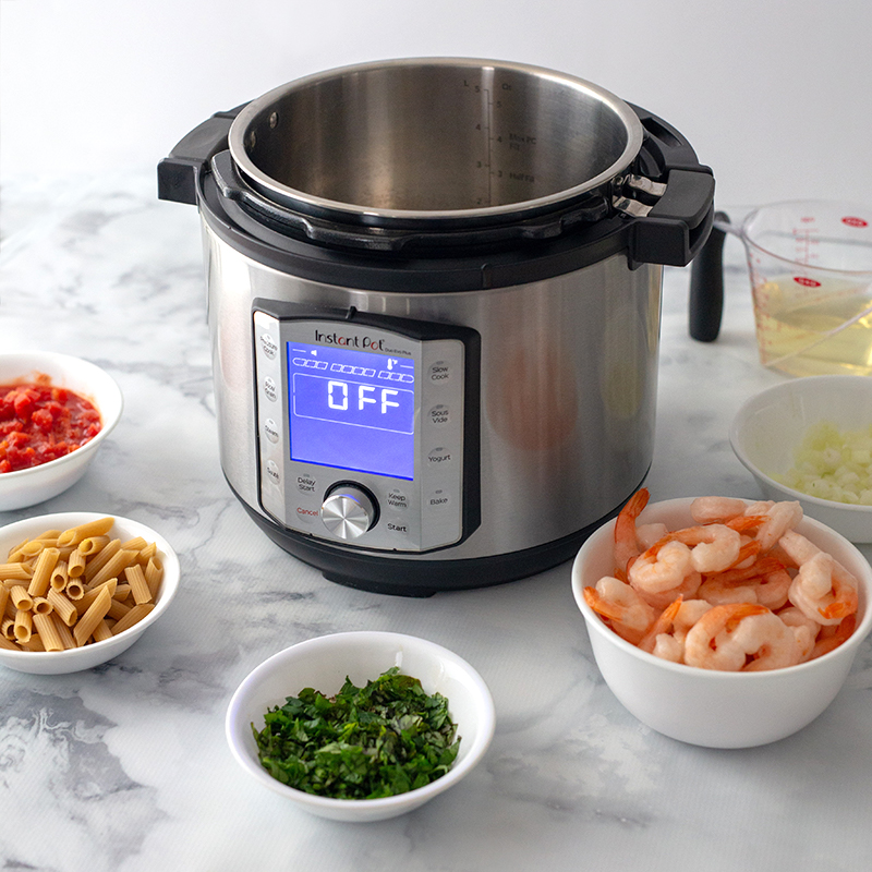 Diced tomatoes, penne pasta, chopped basil, shrimp, and onions in bowls placed in front of an Instant Pot preparing to make Shrimp Diavolo.