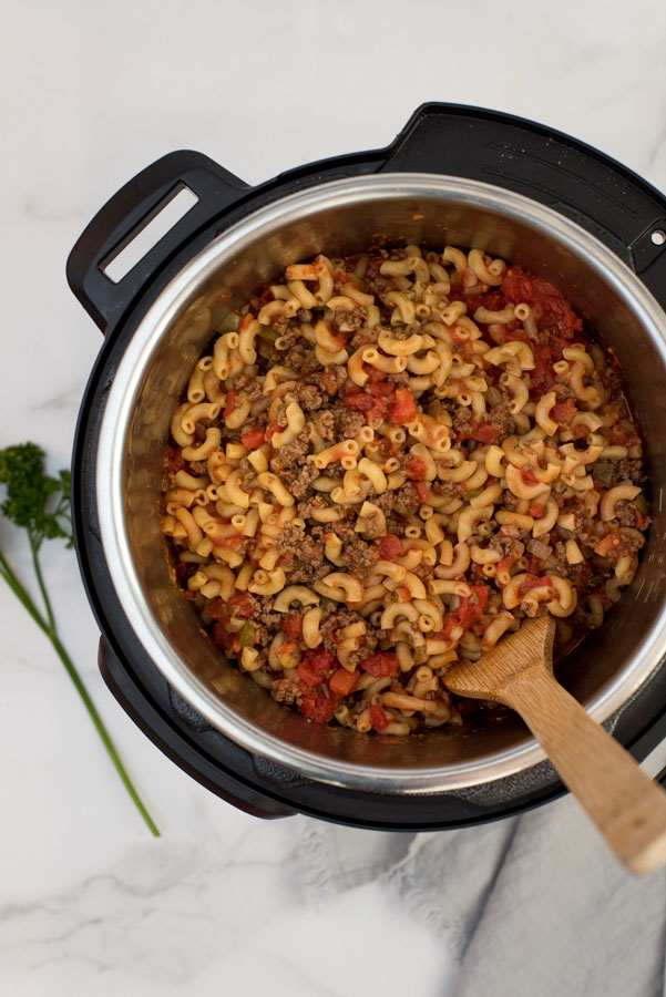 overhead of an instant pot with macaroni noodles, ground beef and tomato sauce to make beefaroni