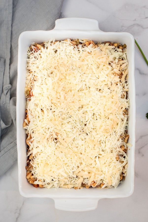 overhead of a white ceramic baking dish with Instant Pot beefaroni casserole covered with shredded Mozzarella cheese, ready for baking