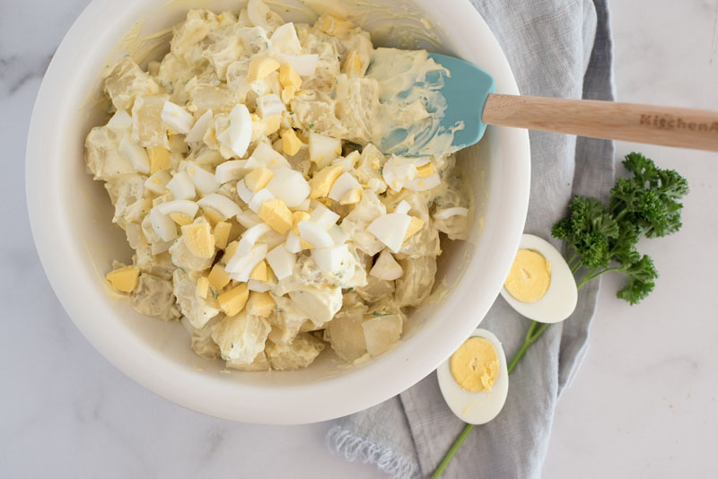 overhead of a white mixing bowl where instant pot poato salad is being mixed with homemade mayonnaise dressing