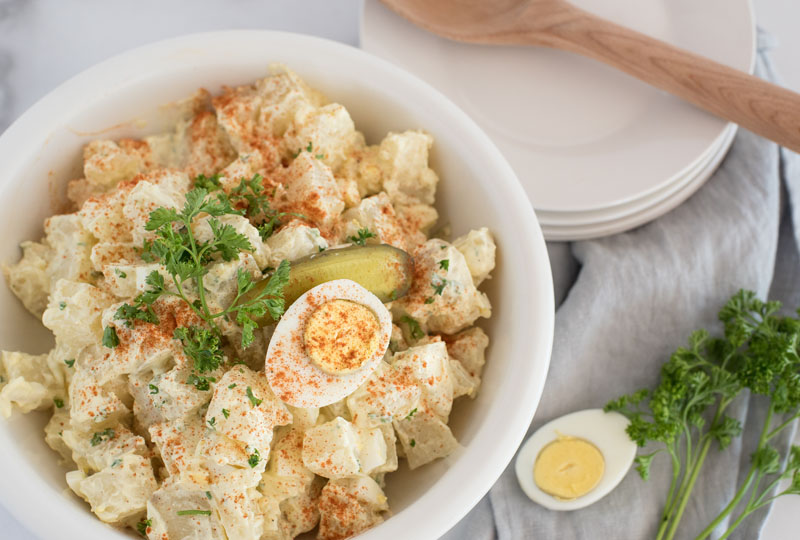 overhead of a white serving bowl with instant pot potato salad with hard-cooked eggs