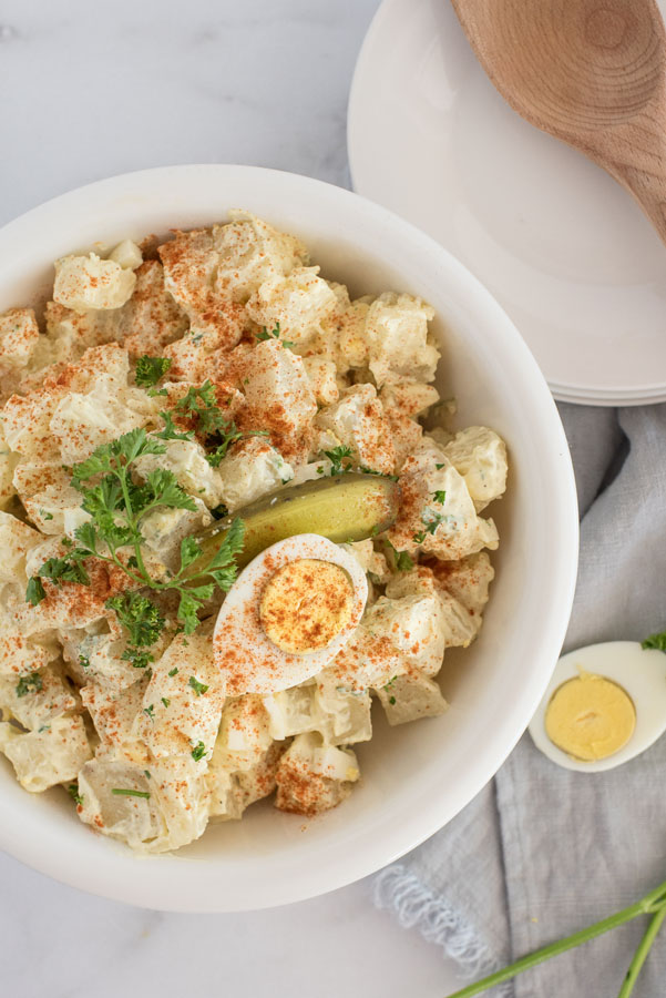 white bowl of quick instant pot potato salad with mayonnaise dressing and hard boiled eggs