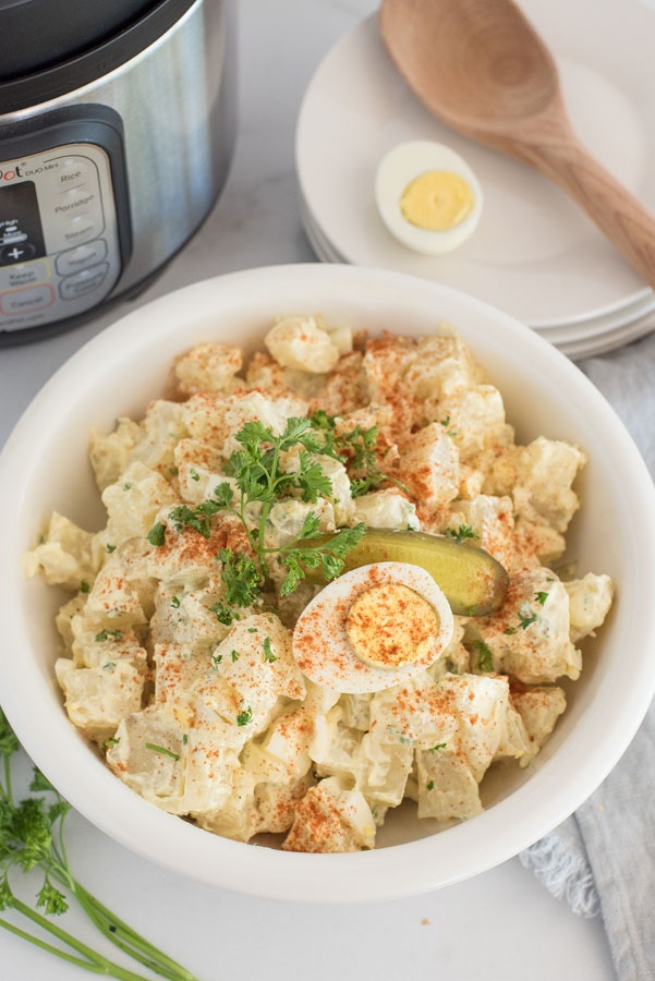 pressure cooker quick potato salad with hard boiled eggs in front of an instant pot with a wooden spoon in the background