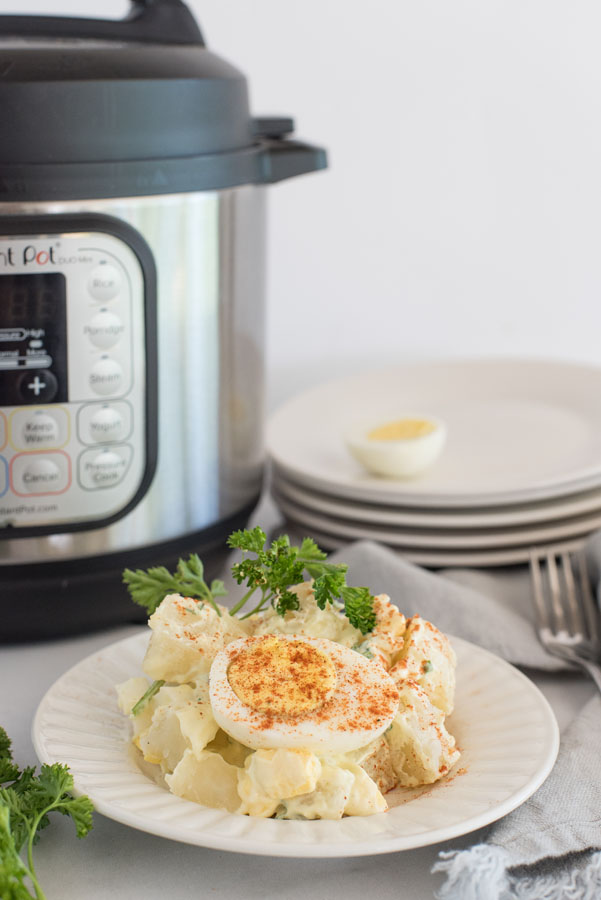 side view of instant pot potato salad with hard boiled eggs and fresh parsley infront of an electric pressure cooker