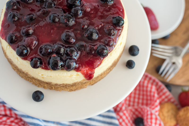 Close up overhead shot of Instant Pot cheesecake topped with berry topping sitting on a white cake stand with red, white, and blue napkins in the background.