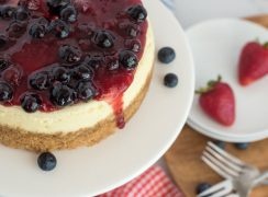 Close up overhead shot of Instant Pot cheesecake topped with triple berry compote and placed on a white cake stand with strawberries on a plate in the background.