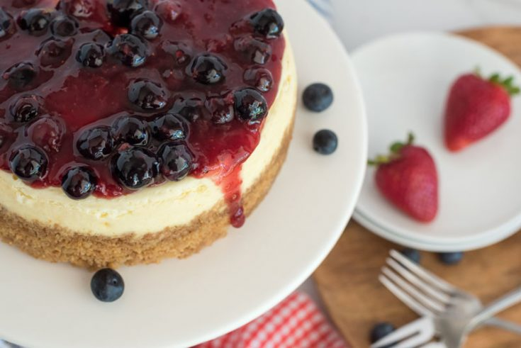 Close up overhead shot of Instant Pot cheesecake topped with triple berry compote on a white cake stand