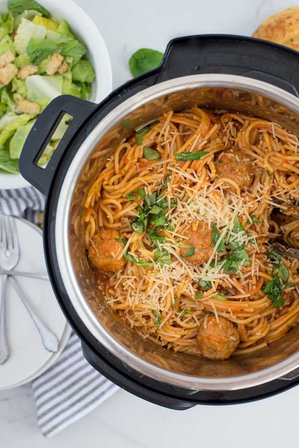 overhead shot of Instant Pot spaghetti and meatballs inside an instant pot, with a green salad on the side