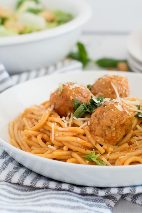 Close up on a white pasta bowl filled with instant pot spaghetti and meatballs with grated parmesan cheese and fresh parsley