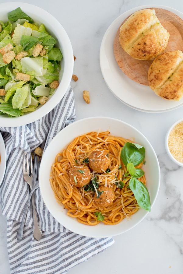 flat lay of a white pasta dish filled with isntant pot spaghetti and meatballs served with a caesar salad and fresh bread rolls on a white marble background
