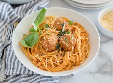 Close up of white bowl with spaghetti and meatballs, spaghetti sauce and fresh basil leaves