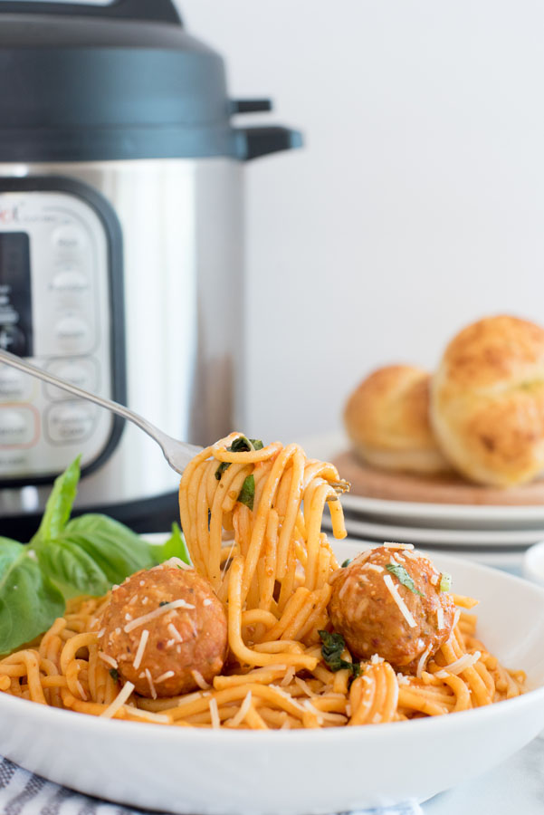 Instant pot spaghetti and meatballs with a bite being taken out with a fork in front of an instant pot electric pressure cooker on a white background