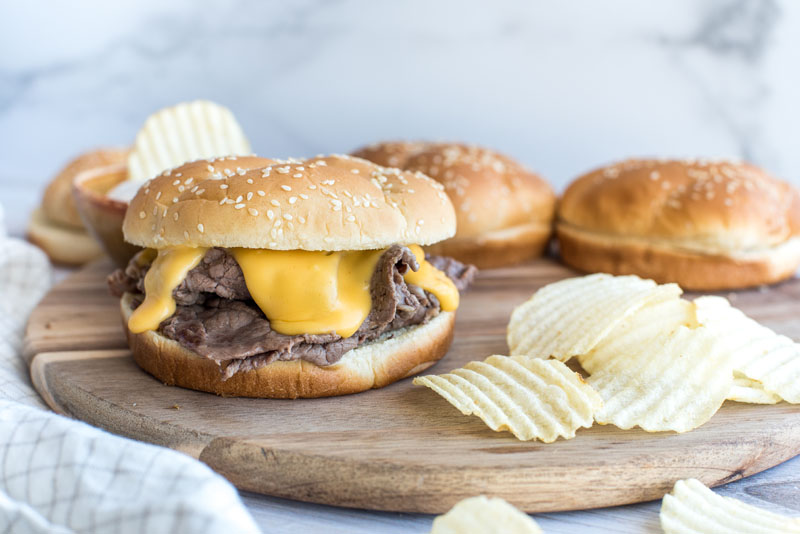 Instant pot shredded beef and melted cheddar cheese sandwiches on a wooden cutting board with ruffle cut potato chips