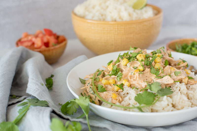 Close up of Instant Pot creamy chipotle chicken served over white rice and garnished with fresh cilantro and served in a white bowl.