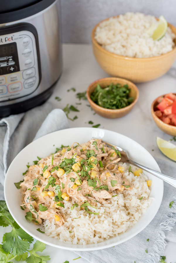 Overhead image of creamy chipotle chicken served over white rice, and garnished with cilantro, served in a white bowl and set in front of an Instant Pot.