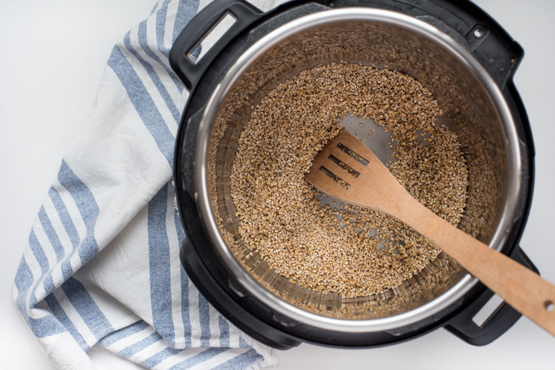 instant pot with dry steel cut oats being toasted in butter with a wooden stirring spoon
