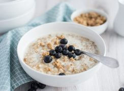 pressure cooker steel cut oats with fresh blueberries in a white cereal bowl with a teal checkered napkin