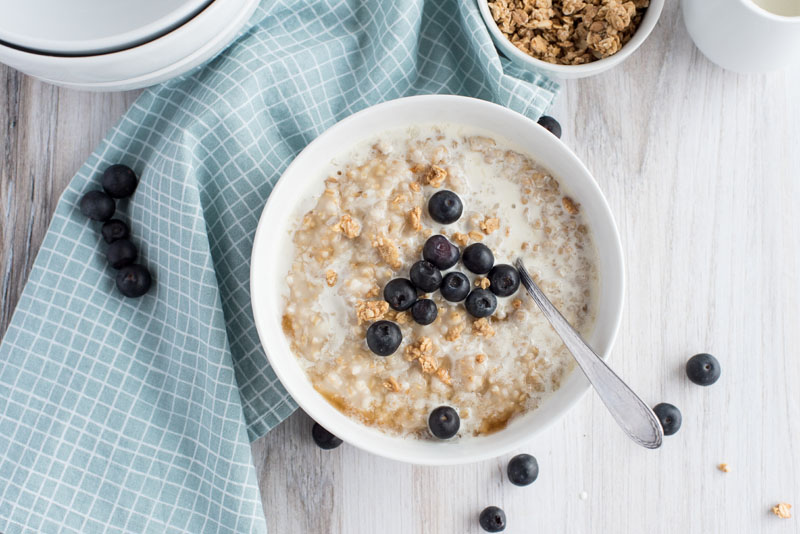 instant pot steel cut oats in a cereal bowl with granola and fresh blueberries