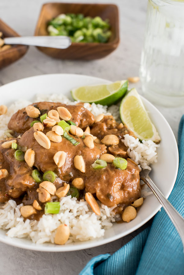 pressure cooker thai chicken thighs with peanut sauce on white rice with a lime wedge