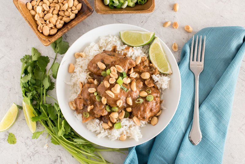 an overhead shot of Instant pot peanut thai chicken with cilantro lime sauce and white rice, with a blue napkin and a fork on it, a sprg on cilantro on the other side, and small dishes of peanuts and green onions at the top
