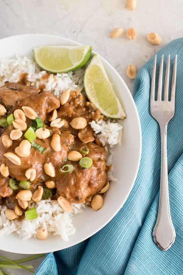 Instant Pot thai peanut chicken thighs with white rice, crunchy peanuts and lime wedges