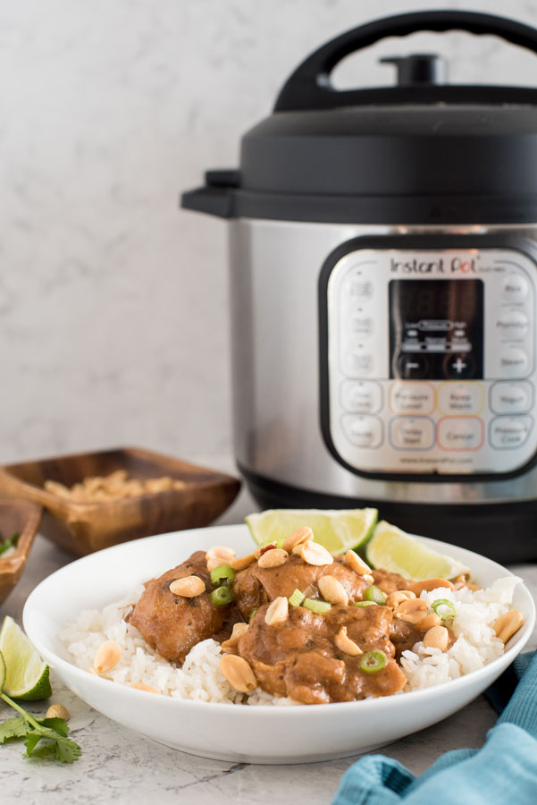 Instant pot/pressure cooker thai chicken thighs with peanut sauce and white rice in front of an elelctric pressure cooker
