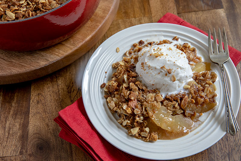 45 degree shot of apple crisp on a white plate, with a big dollop of whipped cream and a toasted topping visible on a white plate