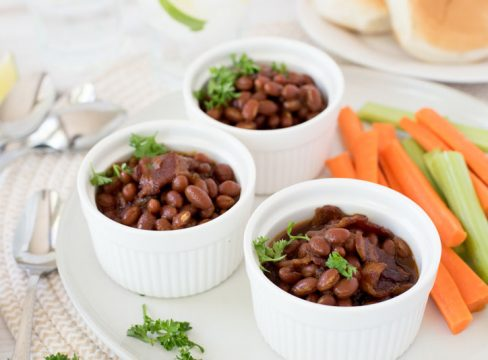 Three white ramekins filled with Instant Pot baked beans served with celery and carrot sticks on the side