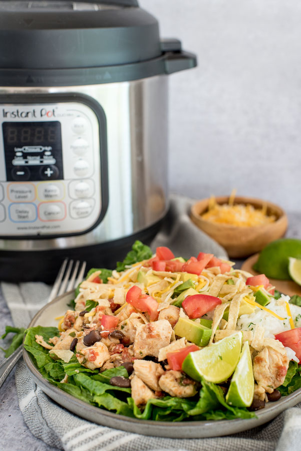 chicken taco salad with rice, dressing and chicken bites in front of an instant pot pressure cooker