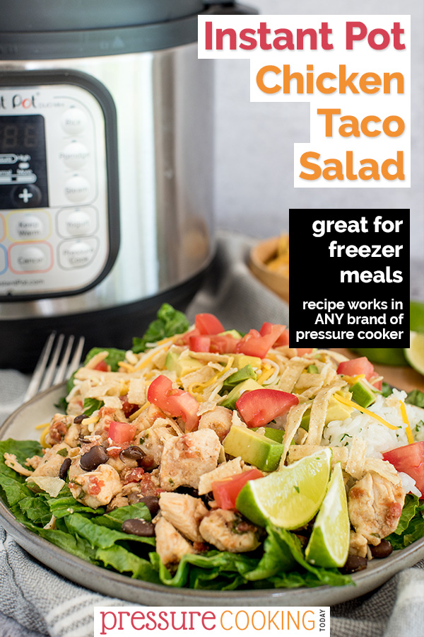Pinterest image promoting pressure cooker chicken taco salad with text overlaid on a 45 degree shot of the salad, drizzled with dressing, cheese, dicied tomatoes, lime wedges on a bed of lettuce, with an Instant Pot in the background via @PressureCook2da