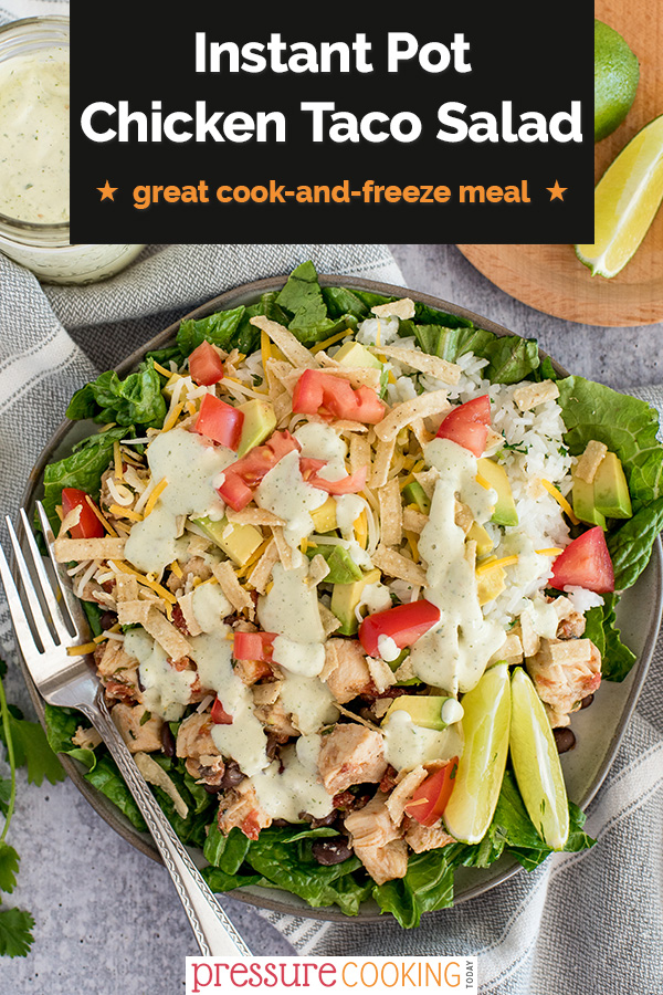 Pinterest image promoting Instant Pot chicken Taco Salad in a black text box, overlaid on a overhead shot of salad, drizzled with dressing, cheese, dicied tomatoes, lime wedges on a bed of lettuce