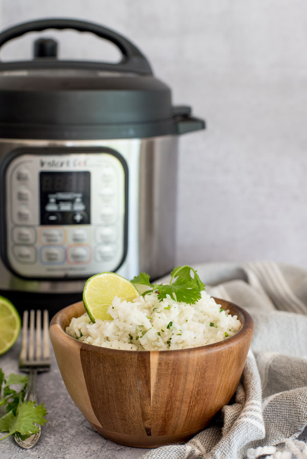 Bowl of cilantro lime white rice in front of an electric instant pot pressure cooker