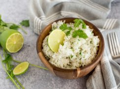 Instant pot cilantro lime white rice in a wooden bowl topped with fresh lime and cilantro